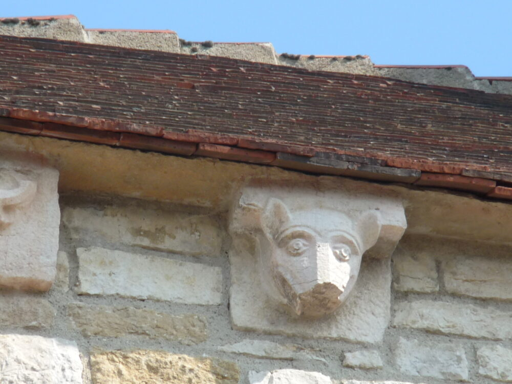 L'un des nombreux modillons visibles sous le toit de l'église